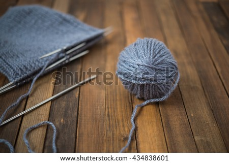 Gray wool yarn ball. Woolen thread with incomplete knitting winter hat on wooden table. Selective focus - stock photo