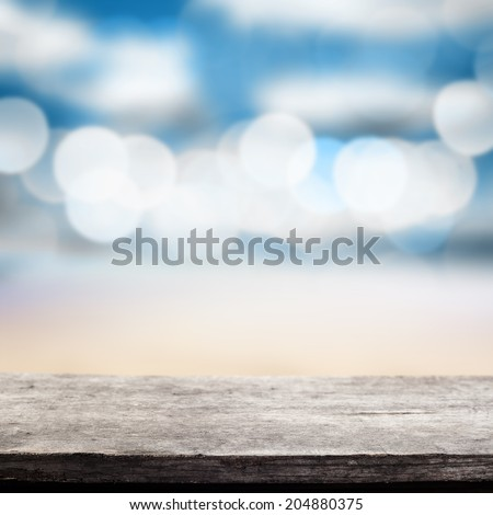 gray worn desk in summer time with sea and beach  - stock photo