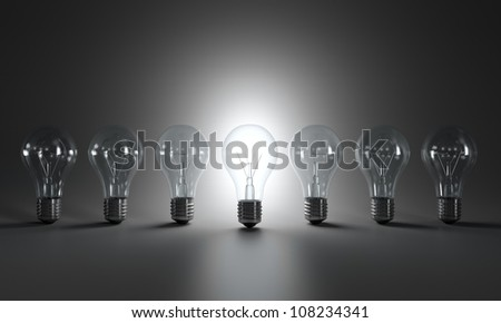 Grayscale image of light bulbs in a row - stock photo