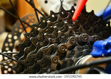 grease lubricating a bicycle gears cogwheel - stock photo