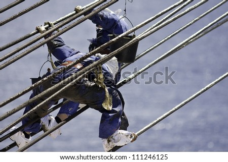 Greasing steel wire of the crane on container vessel by ship's crew. - stock photo