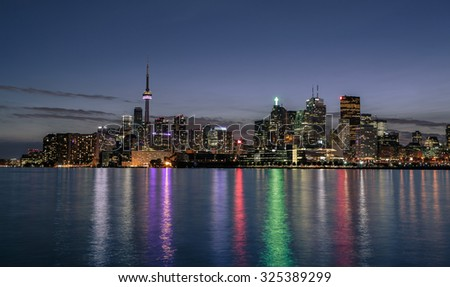 great amazing stunning Toronto city downtown night view from lake Ontario, against dark blue sky with colorful lights reflections in water - stock photo