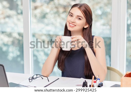 Great aroma.  Vivacious smiling business woman sitting at the table and holding cup while rejoicing in drinking coffee