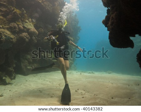 GREAT BARRIER REEF, AUSTRALIA - OCT 28: Scuba diver with camera swims in a coral tunnel October 28, 2009 in Great Barrier Reef, Australia. - stock photo