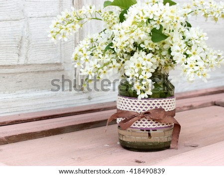 Great bouquet of fresh white cherry tree bird in a glass vase decorated with crochet lace and brown ribbon. Cute pink and white color. Rustic decor elements - stock photo