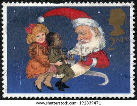 GREAT BRITAIN - CIRCA 1997: a stamp printed in the Great Britain shows Christmas Crackers, Santa as Man in Moon Sharing Cracker with Two Children, circa 1997 - stock photo