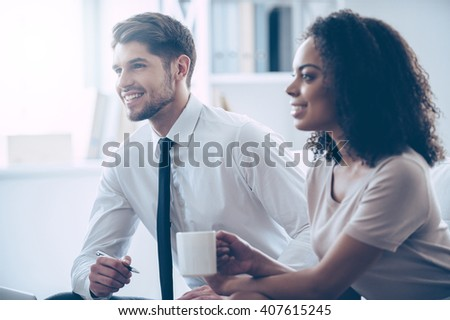 Great business discussion.  Two coworkers looking away with smile while sitting at office  - stock photo