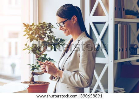 Great business message. Side view of cheerful young beautiful businesswoman in glasses using her smart phone with smile while standing near window sill - stock photo
