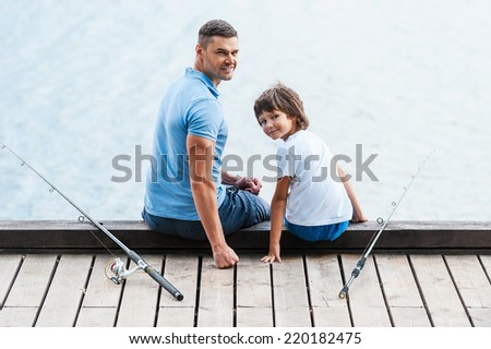 Great day for fishing. Rear view of father and son sitting at the quayside and looking over shoulder while fishing rods laying near them - stock photo