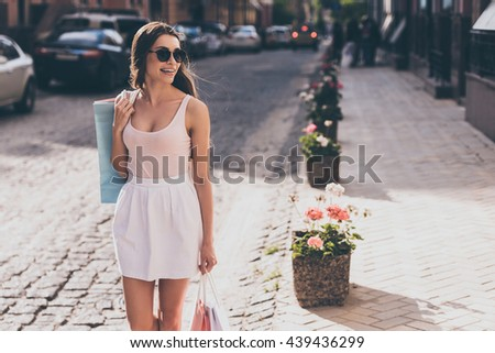 Great day for shopping! Beautiful young woman carrying shopping bags and looking away with smile while walking along the street - stock photo