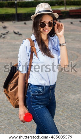 Great day out. Beautiful young smiling woman in sunglasses and bag on a shoulder holding a coffee and looking over shoulder while walking by the street.