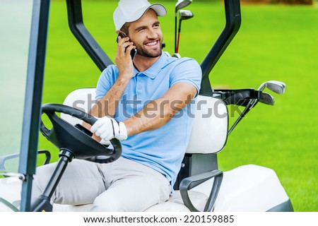 Great day to play golf! Handsome young smiling man driving a golf cart and talking on the mobile phone  - stock photo
