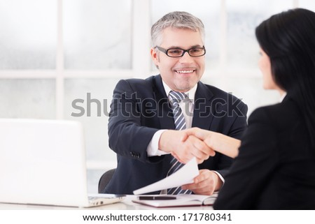 Great deal! Two business people handshaking and smiling while sitting face to face at the table - stock photo
