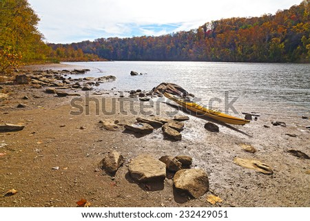 Great Falls National Park in autumn, Virginia USA. A resting kayak on Potomac river rocky banks with colorful autumn trees. - stock photo