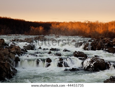 Great Falls on the Potomac near Washington at sunset with the sun illuminating the trees - stock photo
