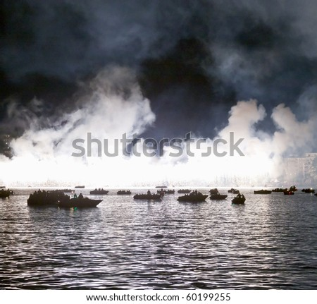Great fireworks exploding over the waters of a lake, with boats near - stock photo