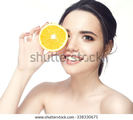 Great food for a healthy lifestyle. Beautiful young shirtless woman holding piece of orange in front of her eye while standing against white background and smile - stock photo