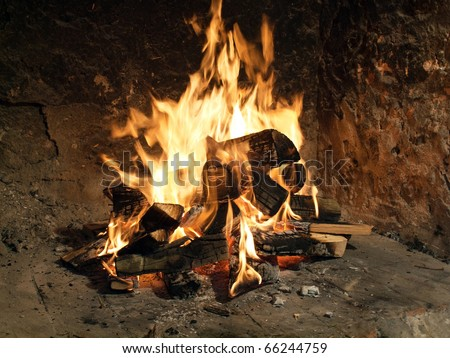 Great glowing fire in a old fireplace - stock photo