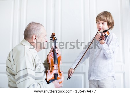 Great grandfather listening to a child playing violin - stock photo