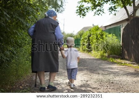Great grandmother and toddler boy holding hands while walking down street in countryside  - stock photo