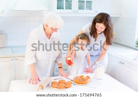 Great grandmother baking an apple pie with her family, young granddaughter and a cute curly toddler girl in a beautiful sunny white kitchen - stock photo