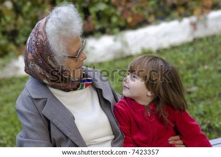 Great grandmother talking to her little grandchild on the bench in the park - stock photo