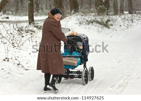Great-grandmother walking with baby boy in pram during snowfall