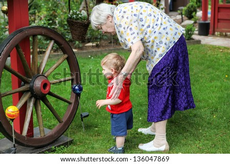 Great-grandmother with little toddler boy and her grandson - stock photo