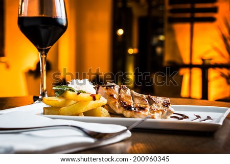 Great grilled pork fillet with red wine glass. - stock photo