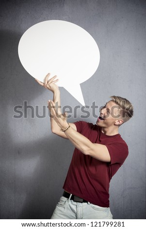 Great idea: Astonished laughing man presenting white blank speech bubble with space for text, isolated on grey background. - stock photo