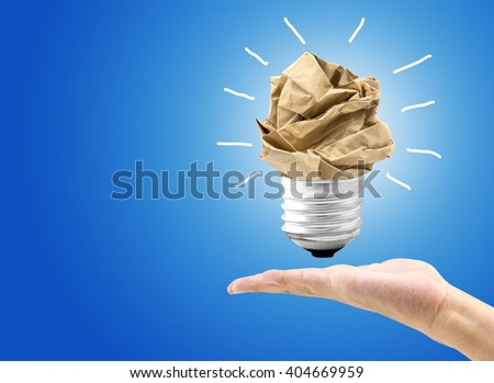 great idea concept with crumpled colorful paper and light bulb hold hand on light background. Creative concept business idea, innovation and solution, creative design. - stock photo