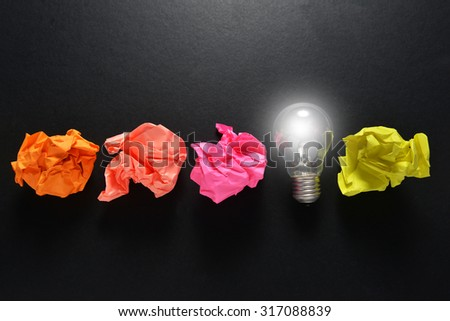 great idea concept with crumpled colorful paper and light bulb on black background - stock photo