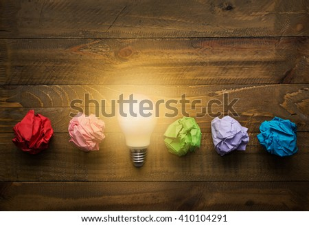 Great idea concept with crumpled colorful paper and light bulb on wooden table - stock photo