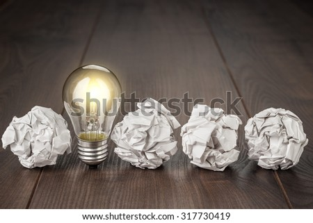 great idea concept with crumpled office paper and light bulb standing on the table - stock photo