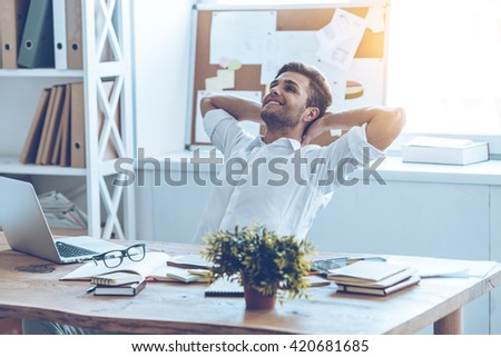 Great job. Cheerful young handsome man keeping hands behind his head and looking away with smile while sitting at his working place - stock photo