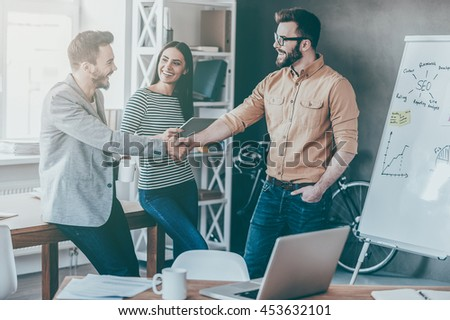 Great job! Confident young man standing near whiteboard and shaking hand to his colleague while young woman standing near them and smiling - stock photo
