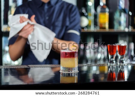 Great job. Selective focus on beautiful red and yellow cocktail on the counter while bartender drying hands with a towel stands behind the bar counter