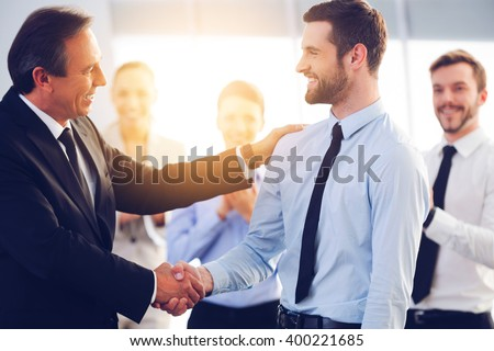 Great job! Two cheerful business men shaking hands while their colleagues applauding and smiling in the background - stock photo