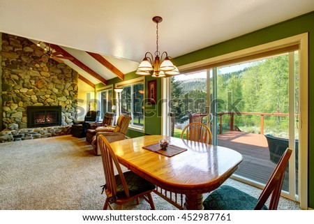 Great living room and dining interior in American country house. Glass sliding doors lead to the walkout deck.