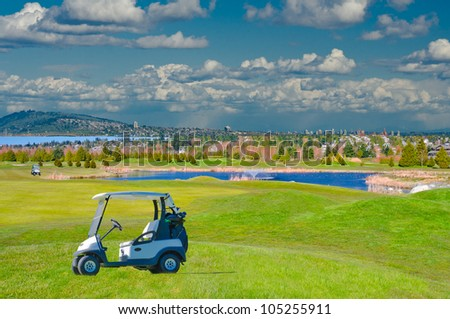 Great looking golf course with two carts, the pond and urban background . - stock photo
