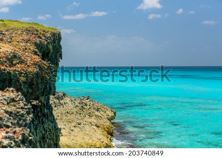 great natural view of tropical background with tranquil ocean, cliff and blue sky - stock photo