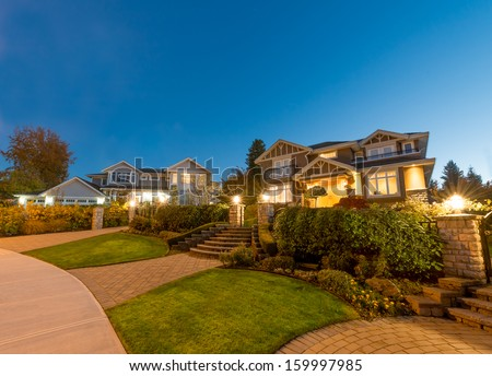 Great neighborhood. Luxury houses with nicely  paved doorway at dusk, night time in suburbs of Vancouver, Canada. - stock photo