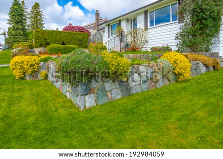 Great neighborhood. Nicely decorated flowerbed, front yard, lawn with colorful bushes as a decorative elements. Landscape design. - stock photo