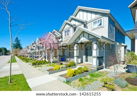 Great neighborhood. Row of the houses, homes with the sidewalk on empty street in suburbs of Vancouver, Canada. - stock photo