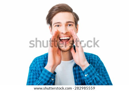 Great news! Cheerful young man holding hands near mouth and shouting while standing against white background  - stock photo