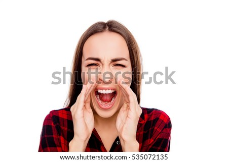 Great news! Cheerful young woman holding hands near mouth and screaming
