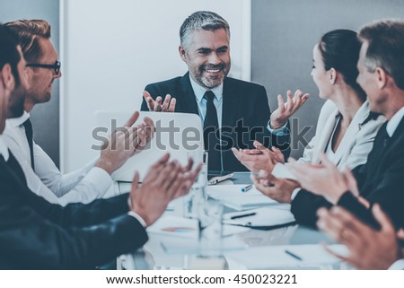 Great news! Confident mature man in formalwear smiling and gesturing while his colleagues applauding to him - stock photo