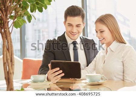 Great news for the case. Two cheerful business colleagues laughing happily enjoying using a digital tablet working at the coffee shop - stock photo
