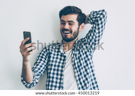 Great news from friend. Happy young man holding smart phone and looking at it with smile - stock photo