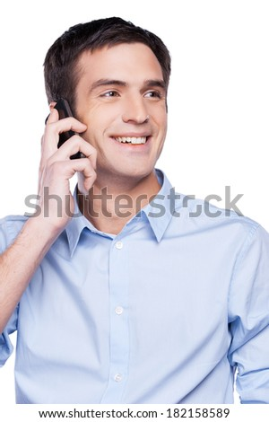 Great news! Handsome young man in blue shirt talking on the mobile phone and smiling while standing isolated on white